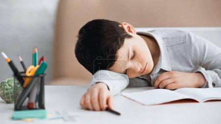 Photo pour Preteen garçon couché près de carnet et de papeterie sur la table - image libre de droit