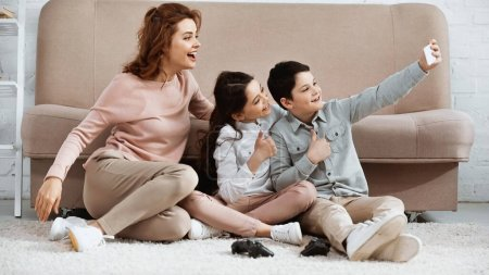 Photo for KYIV, UKRAINE -  APRIL 15, 2019: Smiling kids showing yes gesture while taking selfie near mother and joysticks on floor - Royalty Free Image