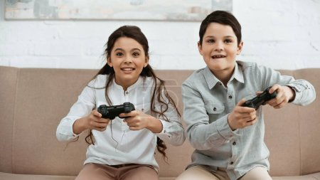 Photo for KYIV, UKRAINE -  APRIL 15, 2019: Positive kids playing video game in living room - Royalty Free Image