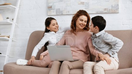 Photo for Smiling mother with laptop hugging kids on couch - Royalty Free Image
