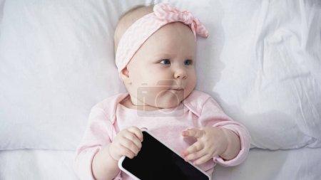 Photo pour Vue du dessus de la jeune fille tenant smartphone avec écran vide tout en regardant loin - image libre de droit