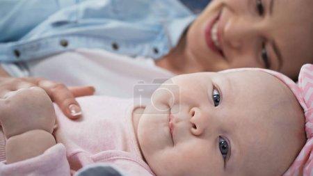 Photo pour Bébé fille regardant la caméra tout en étant couché près de la mère sur fond flou - image libre de droit