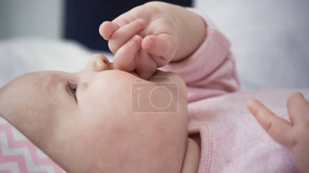 close up of baby girl sucking fingers