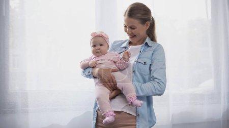 freudige Mutter hält ihre kleine Tochter im Arm