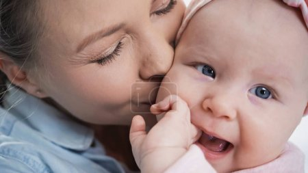 close up of mother kissing infant daughter sucking fingers
