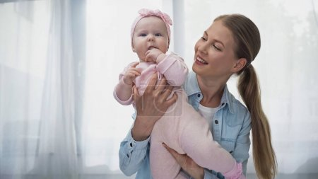 positive woman holding in arms infant daughter in headband with bow