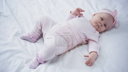 high angle view of baby girl in headband with bow lying on bed