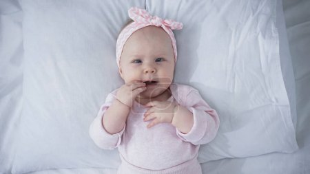 top view of baby girl in headband with bow lying on bed with white bedding