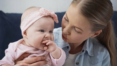Photo pour Mère attentionnée regardant bébé fille sucer les doigts - image libre de droit