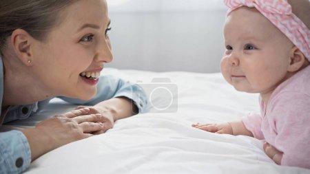 Photo pour Joyeuse mère regardant bébé fille sur le lit - image libre de droit
