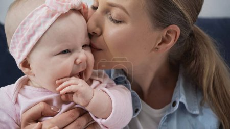 caring mother kissing cheek of baby daughter