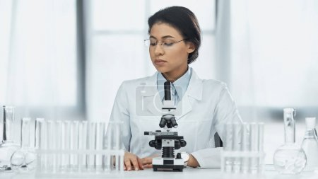 african american scientist in glasses looking at test tubes near microscope in lab