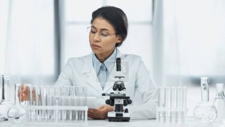 Photo for African american scientist in glasses taking flask near microscope in lab - Royalty Free Image