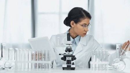 Photo for African american scientist in glasses holding digital tablet near microscope and test tubes in lab - Royalty Free Image