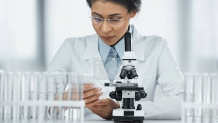 Photo for African american scientist looking and smartphone near microscope in lab - Royalty Free Image
