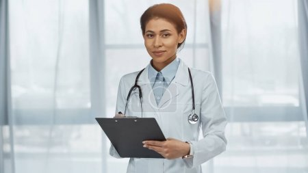 Photo for Cheerful african american doctor in white coat with stethoscope holding clipboard in clinic - Royalty Free Image
