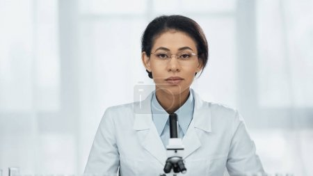 Photo for African american scientist in glasses looking at camera near microscope - Royalty Free Image