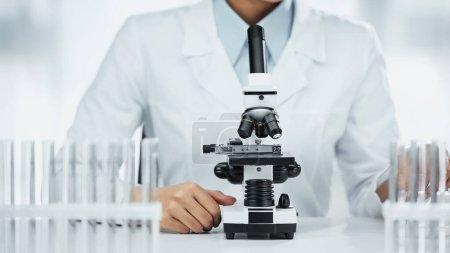 Foto de Vista recortada del científico afroamericano cerca del microscopio y tubos de ensayo en laboratorio - Imagen libre de derechos