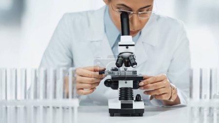 Photo pour Scientifique afro-américain regardant à travers le microscope près des éprouvettes en laboratoire - image libre de droit