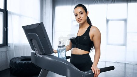 sweaty sportswoman with towel on treadmill looking at camera near sports bottle with water in gym