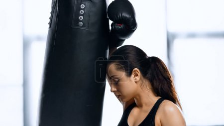 tired sportswoman in boxing glove and with closed eyes resting near punching bag in gym