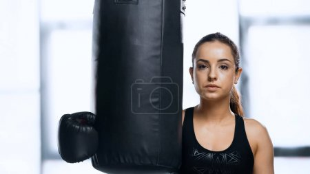 young sportswoman in boxing glove resting near punching bag in gym