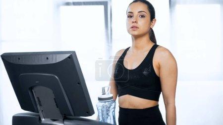 jeune femme en vêtements de sport faisant de l'exercice sur tapis roulant près d'une bouteille de sport avec de l'eau dans la salle de gym