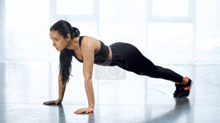junge Frau in Sportbekleidung beim Planken im Fitnessstudio