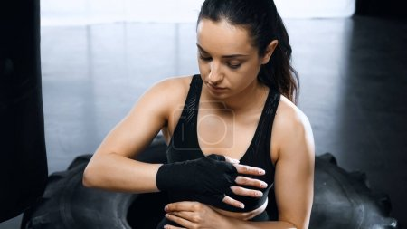 young brunette sportswoman putting on hands boxing bandages