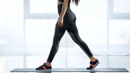 partial view of sportive woman working out on fitness mat in sports center