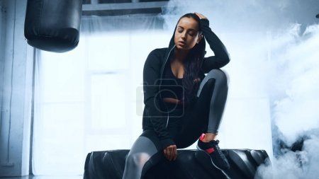 sporty woman in hoodie sitting on tire near punching back and smoke behind