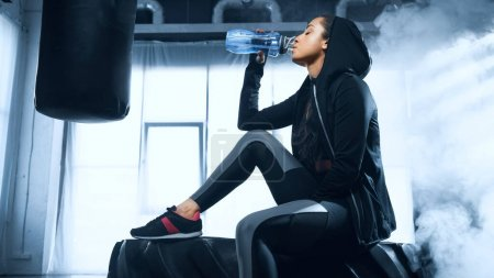 sportswoman in hoodie sitting on tire and drinking water from sports bottle
