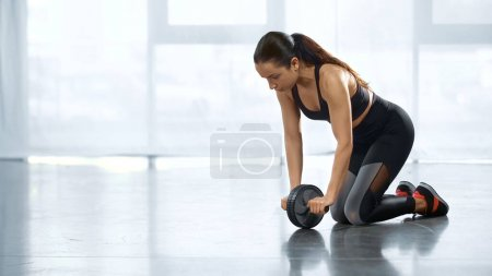 sweaty young sportswoman training with ab wheel in gym