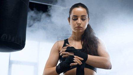 young brunette sportswoman bandaging hands near punching bag