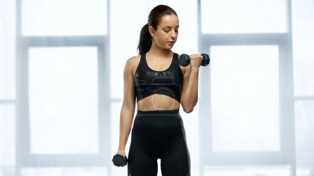 Photo for Strong sportswoman in crop top working out with dumbbells - Royalty Free Image