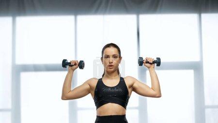 junge Sportlerin im Crop Top beim Training mit Kurzhanteln