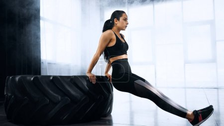 Photo for Young brunette sportswoman exercising near tire in gym - Royalty Free Image