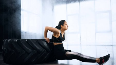 brünette und sportliche junge Frau turnt in Turnhalle in Reifennähe