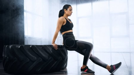 brunette and sportive woman exercising near tire in gym