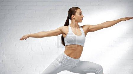 Deportiva en ropa deportiva blanca de entrenamiento en casa
