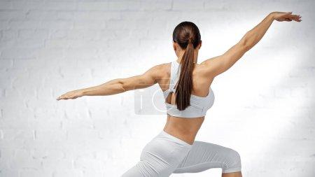Sportlerin in weißem Sporttop trainiert zu Hause