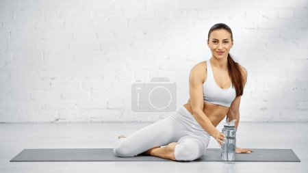 Photo for Smiling sportswoman looking at camera near sports bottle on yoga mat - Royalty Free Image