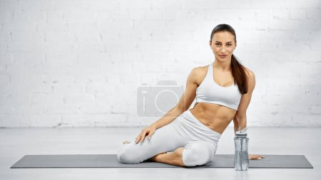 Photo for Young sportswoman looking at camera on yoga mat near sports bottle on floor - Royalty Free Image