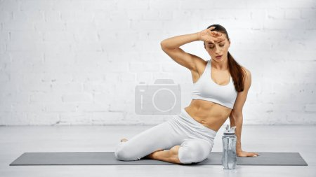 Tired woman sitting on yoga mat near sport bottle