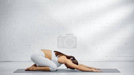 Photo pour Vue latérale de la femme assise dans la pose de l'enfant sur le tapis de yoga - image libre de droit