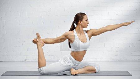 Jeune femme étirant dans la pose de yoga sur le tapis