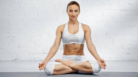 Photo for Smiling woman in lotus pose meditating on yoga mat - Royalty Free Image
