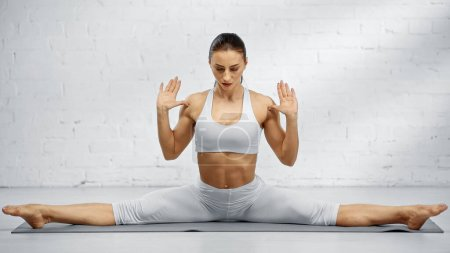 Photo for Barefoot woman in seated straddle pose on yoga mat - Royalty Free Image