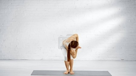Brunette woman standing in chair twist yoga pose