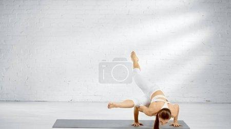 Junge Frau balanciert auf Yogamatte